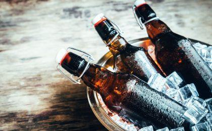 Tre flaskor i i en skål med is.