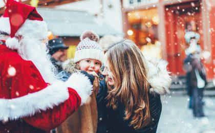 Mamma och barn hälsar på jultomte.