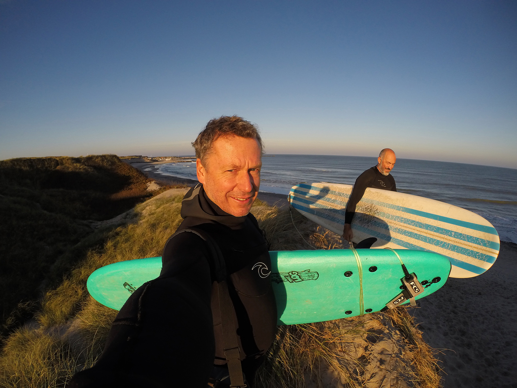 Två taggade surfare på väg in i vattnet.